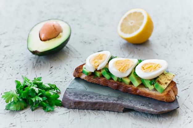 アボカド、レモン、チリ、またはパプリカと卵の灰色の背景のトースト