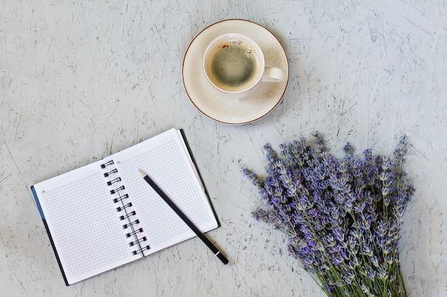Утренняя кружка кофе, пустой блокнот и фиолетовые цветы лаванды на сером фоне