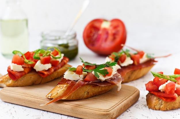 イタリアの前菜 - トマト、チリ、ソーセージ、木の板にチーズのブルスケッタ