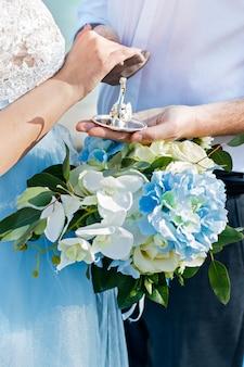 新婚夫婦はリングを着ます。結婚式。花嫁のブーケ指輪を新郎新婦。