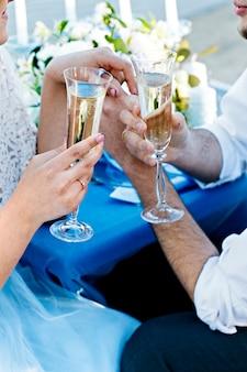 メガネで新婚夫婦。結婚式。花嫁のブーケ指輪を新郎新婦。スパークリングワインのグラスと新婚夫婦。