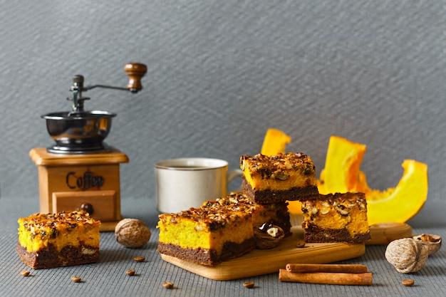 ハロウィーンの食べ物。ナッツとカボチャの層が付いている自家製チョコレートブラウニー。ケーキとコーヒー。
