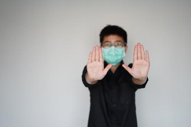 世界的なコロナウイルスの大流行を防ぐために顔の衛生マスクを身に着けている若い男。彼は手停止を持ち上げて感染し、彼は呼吸器系の問題を抱えており、症状は同じインフルエンザです。