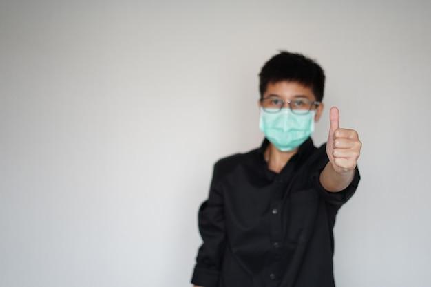 世界的なコロナウイルスの大流行を防ぐために顔の衛生マスクを身に着けている若い男。彼は私たちが生き残る偉大な手を持ち上げます。