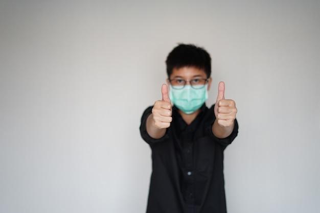 世界的なコロナウイルスの大流行を防ぐために顔の衛生マスクを身に着けている若い男。彼は私たちが生き残るために両手を大きく持ち上げます。