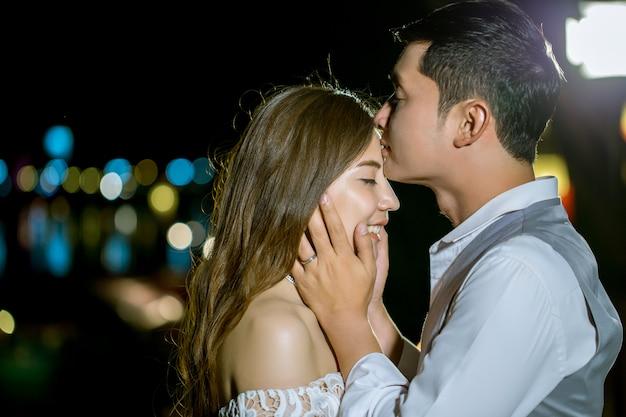 アジア人の男性が彼のガールフレンドの頭にキスします。甘い夜に。