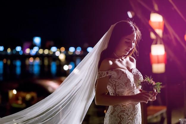 美しい花嫁はロマンチックな夜に一人で立っています。