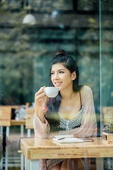 一人のアジア人女性が喫茶店でコーヒーを飲みながら、木製のテーブルの上にノートと携帯電話があります。