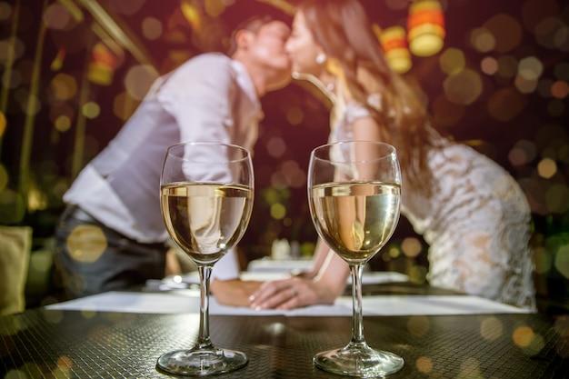 Два бокала вина ставят на стол. азиатские пары целуются вместе на размыли фоне.