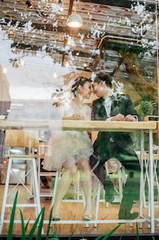 レストランのガラスを通して見る。笑っている顔と一緒に話しているアジアの花嫁とアジアの花嫁がいます。