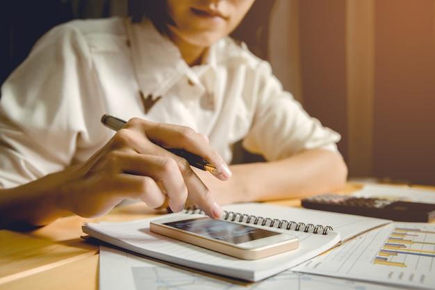 Рука бизнес-леди держа ручку и касающий экран умного телефона для искать коммерческие данные.