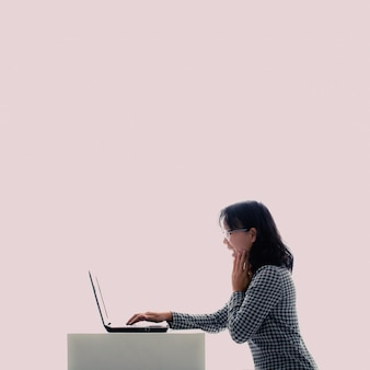 眼鏡をかけているアジアの女の子ノートパソコンを使用しながら彼女は楽しんでいます。