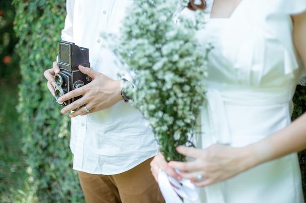 Мужчина держит классическую камеру он стоит рядом со своей девушкой