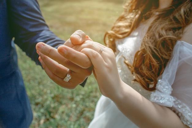 結婚式の日に一緒に手を繋いでいるアジアカップル