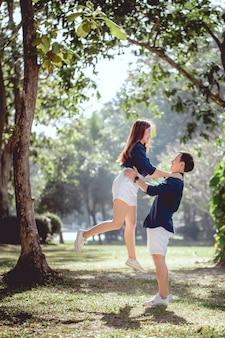 昼間の公園で素敵なアジアカップルの幸せな時間、男は彼のガールフレンドを保持します。