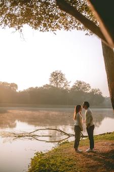 朝、湖のほとりの素敵なアジアのカップルの甘い時間。