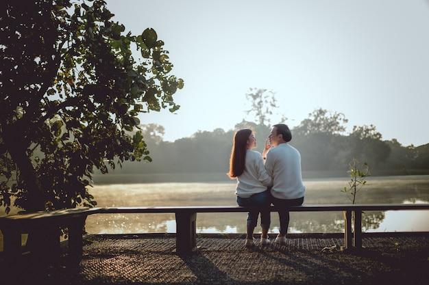 朝、湖のそばで彼氏の頭に触れるアジアの少女。