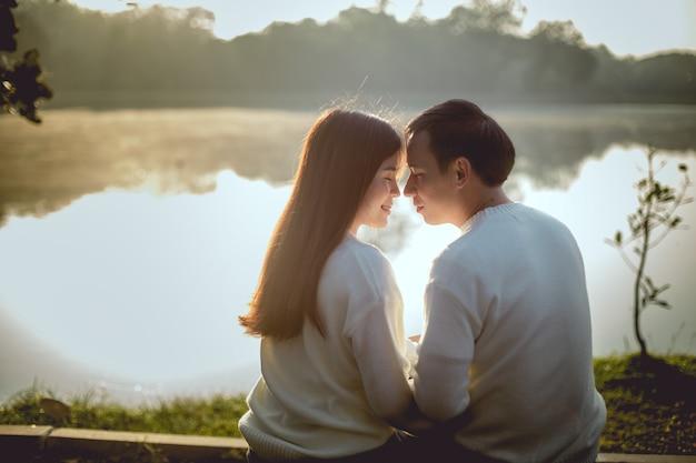 Романтичное время симпатичных азиатских пар в озере паркует на утре. они будут целоваться вместе.