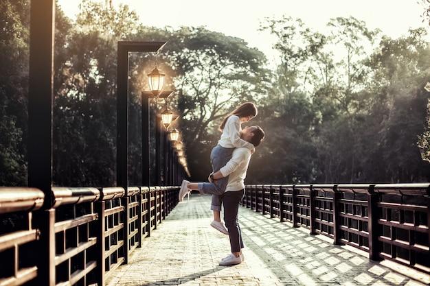 強いアジア人の男は、ランプでずっと彼女のガールフレンドを橋で支えています。
