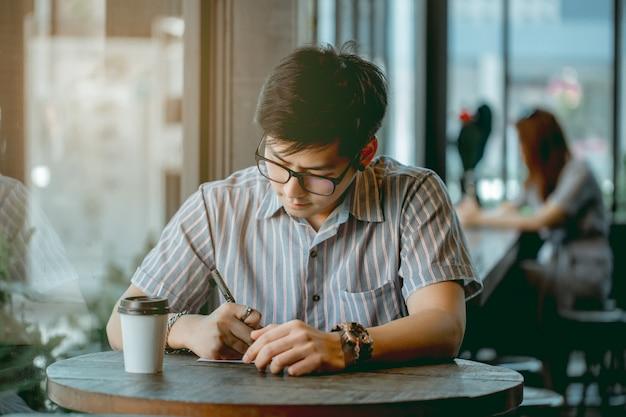 座っていると考えて何かを書くメガネのアジア人。