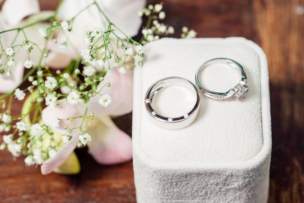 ダイヤモンドのカップルの結婚指輪はガラスの上に置かれます。自然があります植物は装飾です。
