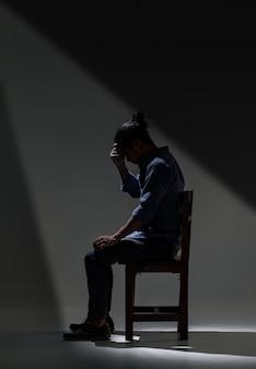 アジア人男性が暗闇の中でうつ病に苦しんでいます。