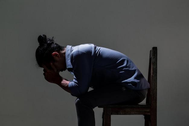 Азиатский человек страдает от депрессии в темноте.