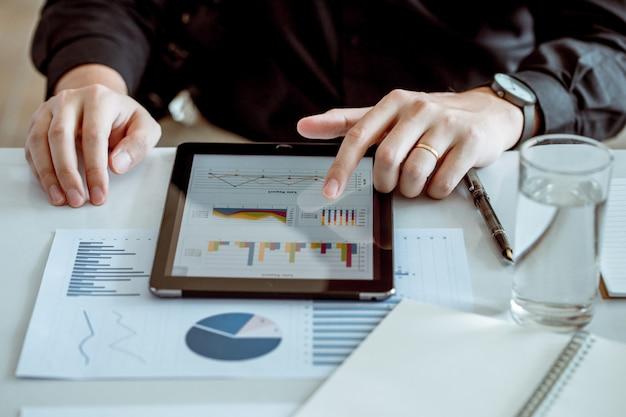 ビジネスマンは、分析経済学の言葉のために接続するタブレットコンピューターを使用します。彼は結婚しています。
