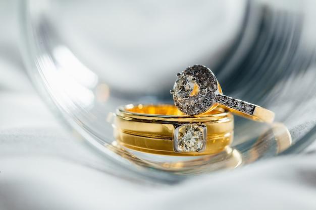 ダイヤモンドのカップルの結婚指輪はガラスに置かれています。