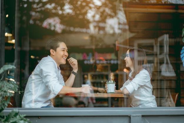 Азиатская пара, счастливо говорить в кафе в дневное время.