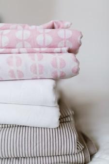 清潔でアイロンをかけたリネンの積み重ねがベッドの上にあります