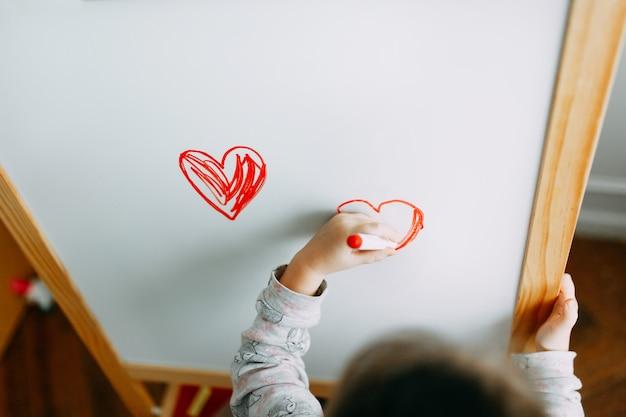 女の子は白い黒板にマーカーで心を描きます。母の日。バレンタイン・デー