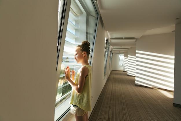 ホテルの廊下にいる姉妹の女の子たちは、ブラインドを通して輝く太陽の下で喜びます。