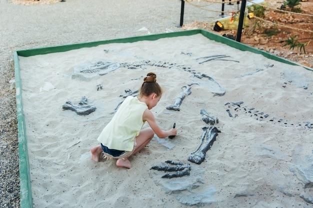 白人の女の子は、アドベンチャーパーク、セレクティブフォーカスで砂を掘る楽しみを持っています