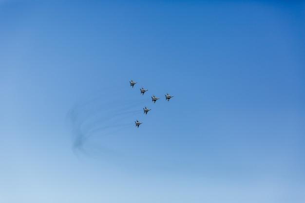 Треугольное образование группы из шести российских военных самолетов-истребителей, летящих высоко в синем небе