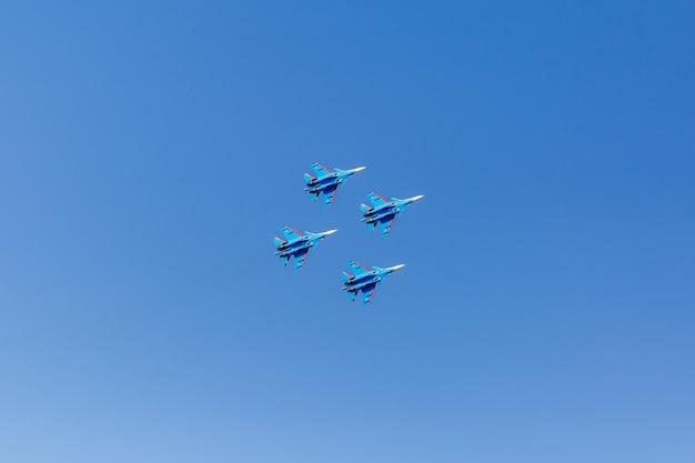 Квадратное формирование группы из четырех российских военных самолетов-истребителей, летящих высоко в синем небе