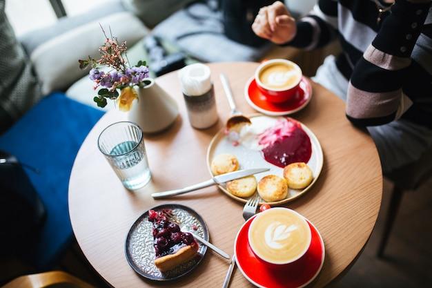 Вид сверху на стол в кафе. две чашки кофе и десерт