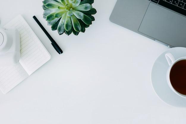 ノートパソコン、オフィスの植物とペン、ミニカメラ、紅茶のカップとノートブックと白い事務机。コピースペース平面図、平面レイアウト