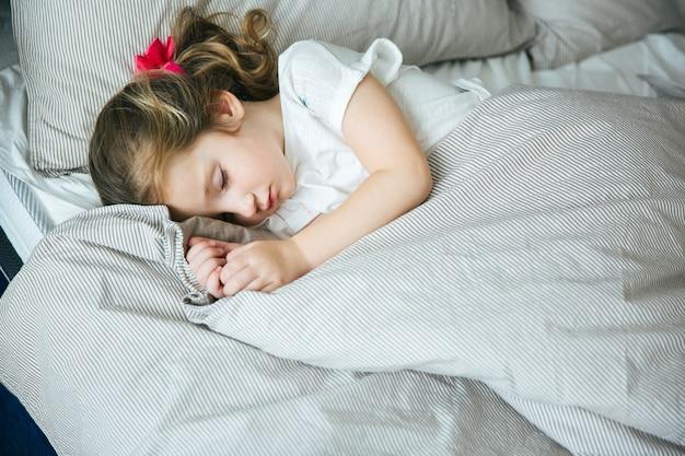 Очаровательная маленькая девочка спит в постели в пижаме под одеялом дома, спокойно и мирно