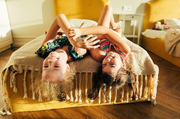 Сестра развлекается в постели и делится моментами любви. маленькие девочки весело вместе в постели. маленькие девочки играют дома на кровати.