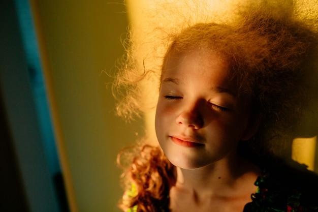 Выборочный фокус. маленькая блондинка милая девушка улыбается с закрытыми глазами. закат теплым светом. солнечный свет в волосах. лето счастливое время.