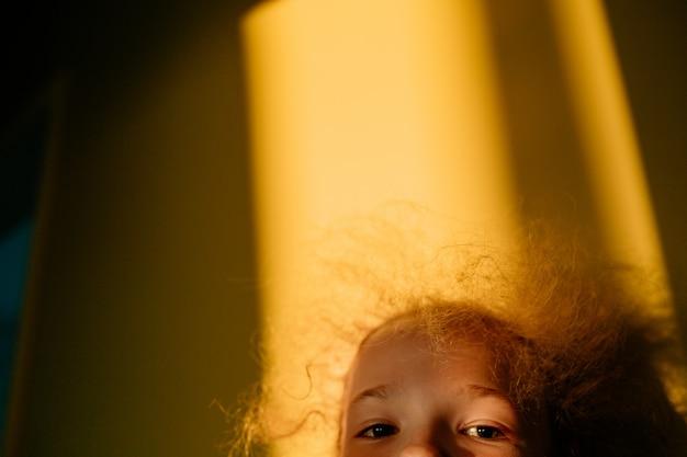 Выборочный фокус. маленькая белокурая милая девочка играет в прятки. закат теплым светом. солнечный свет в волосах. лето счастливое время.
