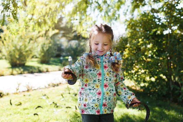 Маленькая белая счастливая девушка с двумя косичками в разноцветной куртке собирает стручки с дерева в теплый осенний день