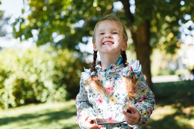 Маленькая белая счастливая девушка с двумя косичками в разноцветной куртке смотрит в камеру и улыбается в теплый осенний день