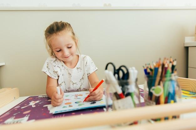 小さな女の子は彼の机に座って学ぶことを幸せです。ホームスクールのコンセプト。教育コンセプト。子供の学習の背景。幼児の手作りゲーム。幼稚園教育。