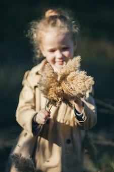 Девушка в бежевом плаще держит букет из камыша
