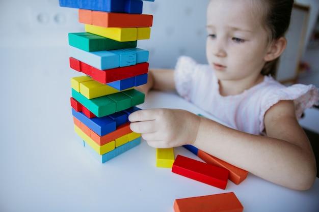 Ребенок играет с красочными деревянными кирпичами на белом фоне стола