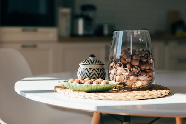Орехи макадамии лежат в миске на кухне, жесткий утренний свет