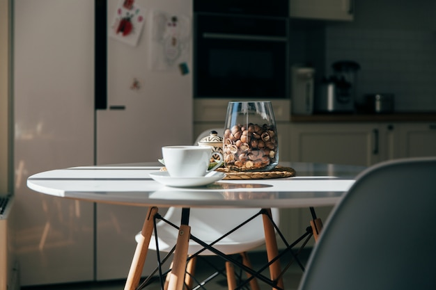 Орехи макадамии в миске и чашке чая или кофе стоят на кухонном столе, жесткий утренний свет