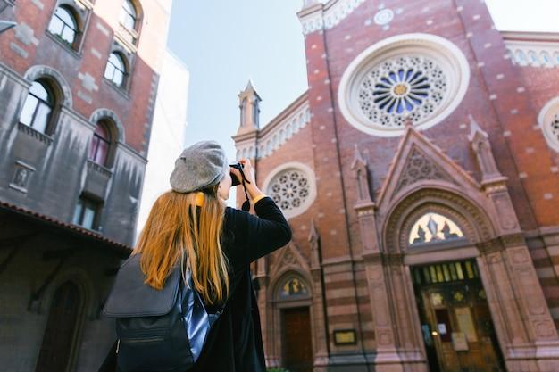 秋の休暇中に教会のカメラで旅行写真を撮る観光客女性